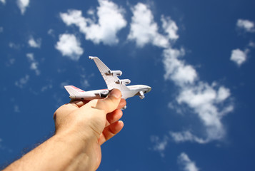close up photo of man's hand holding toy airplane against blue s