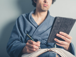 Man in bathrobe using tablet and taking notes