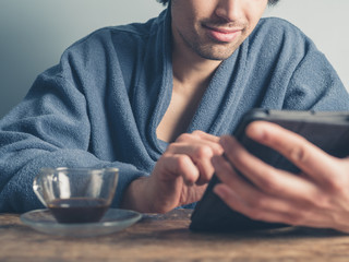Man in bathrobe having coffee and using tablet