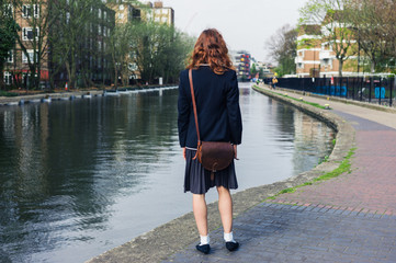 Woman in skirt and jacket sanding by canal