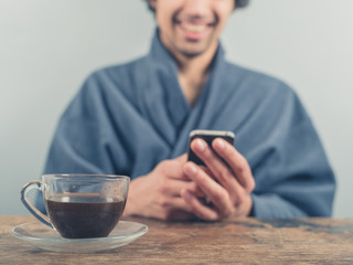 Man in bathrobe using smart phone and drinking coffee