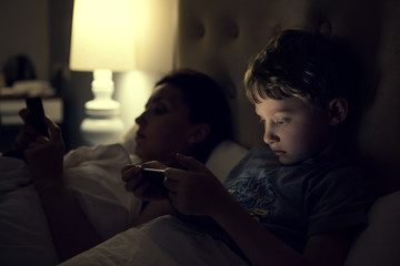 Mother with using modern devices before sleep