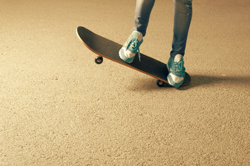 Female on skateboard legs and a lot of copyspace on asphalt