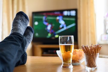 TV watching (football match) with feet on table and snacks