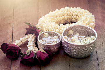 beautiful Thai garland flowers (jasmine and roses) and water in