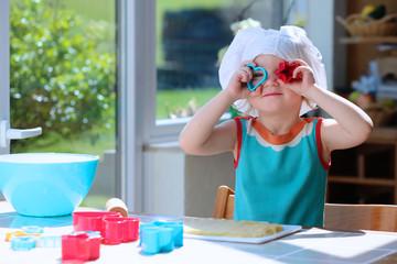 Happy toddler girl in chef hat preparing tasty cookies