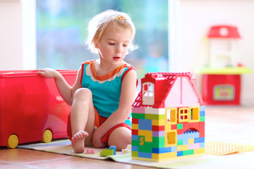 Blonde toddler girl playing with construction blocks