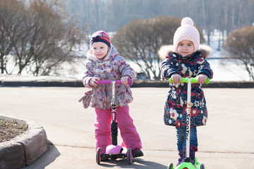 Two girls playing in the park and riding on scooter