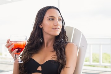 Pretty brunette sitting on a chair and drinking cocktail