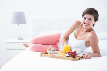 Happy brunette having her breakfast in bed