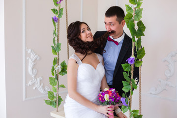 Just married play, bride sitting on a swing with the vine