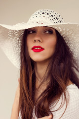 Close-up portrait. White straw hat. Sensual red lips. Boho style