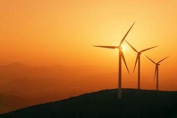 Foto auf Acrylglas Mühlen wind turbines silhouette on mountain at sunset