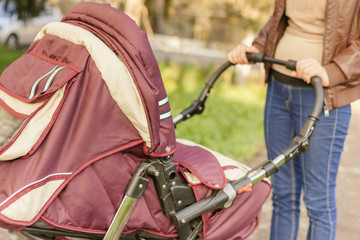 happy mother at outdoor shakes a baby carriage