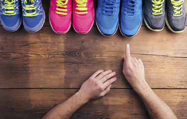 Various running shoes laid on a wooden floor background