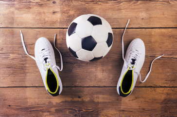 Football boots and ball laid on a wooden floor background