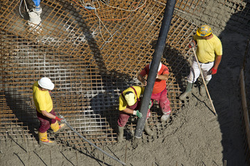 Construction workers casting foundations of hydro power plant