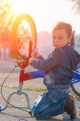 Little boy is pumped European wheel of his bike, sitting on the