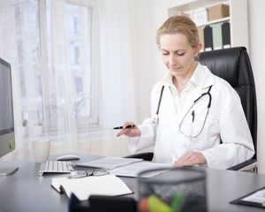Female Doctor Reading her Written Medical Reports