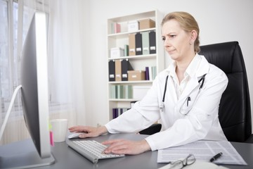 Female Doctor Accessing Information Through Online