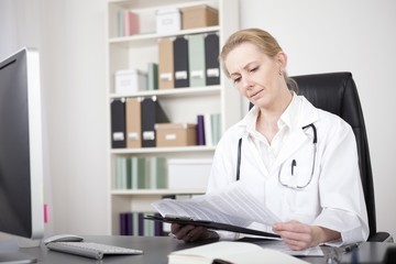 Woman Doctor Reading Medical Reports at her Office