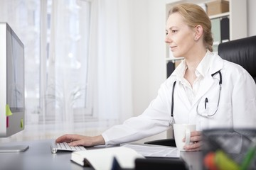 Happy Woman Physician Surfing Internet on Computer