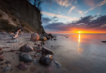 Cliff on sea shore at sunrise. Baltic sea long exposure photo Wall mural