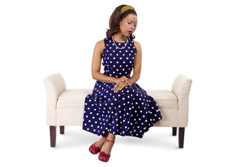 woman wearing a blue polka dot dress looking sad