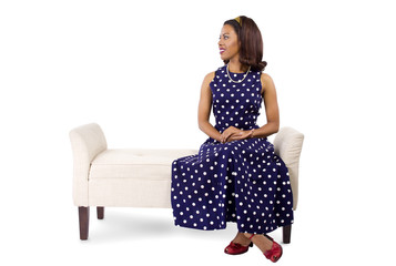 woman wearing a blue polka dot dress sitting on a chaise