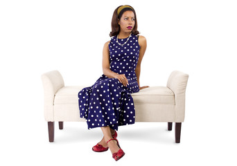 woman wearing a blue polka dot dress looking bored