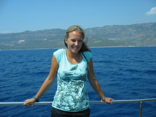 Счасливая девушка на яхте улыбается солнцу и ветру