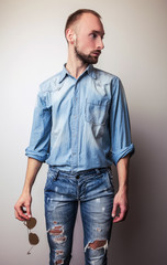 Young handsome man in jeans clothes. Studio fashion portrait.