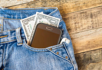 Dollar money and smart phone in pocket blue jeans