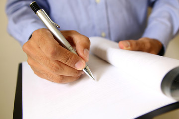 Businessman at office desk signing a contract