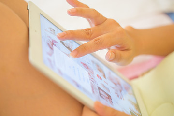 Hand of Asian girl playing Tablet.