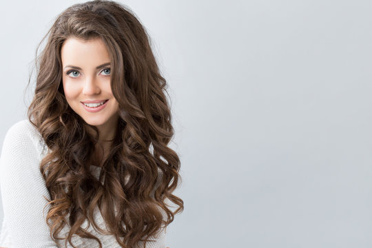 Portrait of a beautiful young woman with wavy hair.