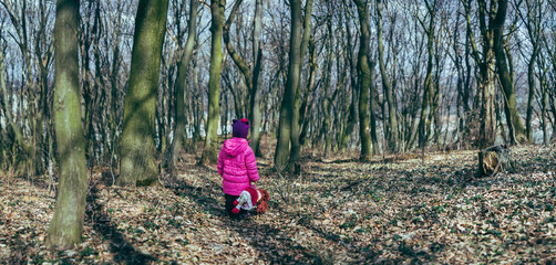 Baby girl with a doll in the woods.panorama