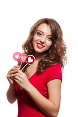 Brunette woman holding lollipops