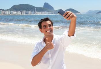 Lachender junger Mann macht ein Selfie an der Copacabana