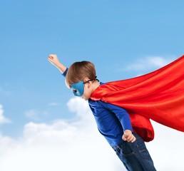 Kid. Superhero kid against blue sky background. Girl power