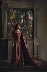 Woman with red hair wearing elegant royal garb