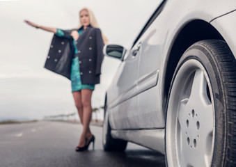 Lady in high heel shoes with broked car on the road