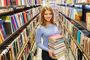 happy student girl or woman with book in library