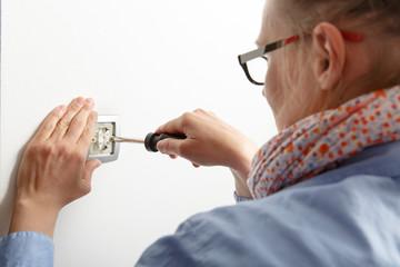 Businesswoman installing a light switch