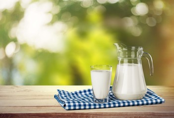Milk. A glass of milk and a milk jug on plaid tablecloth.