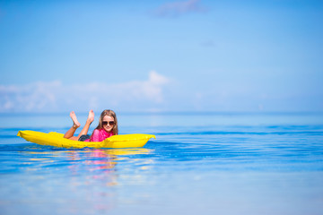 Adorable girl with inflatable air mattress in outdoor swimming
