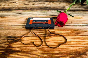 rose and vintage audio cassette with loose tape shaping two hear