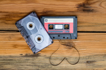 Vintage audio cassette with loose tape shaping two hearts on a w