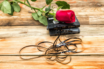 rose and vintage audio cassette on a wooden background.