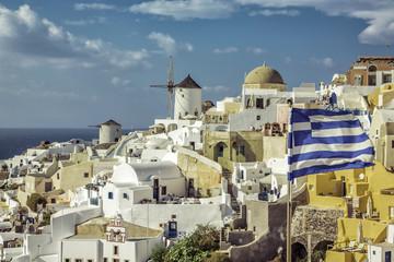 Fototapeta Village of Oia against greek waving flag, Santorini ,Greece